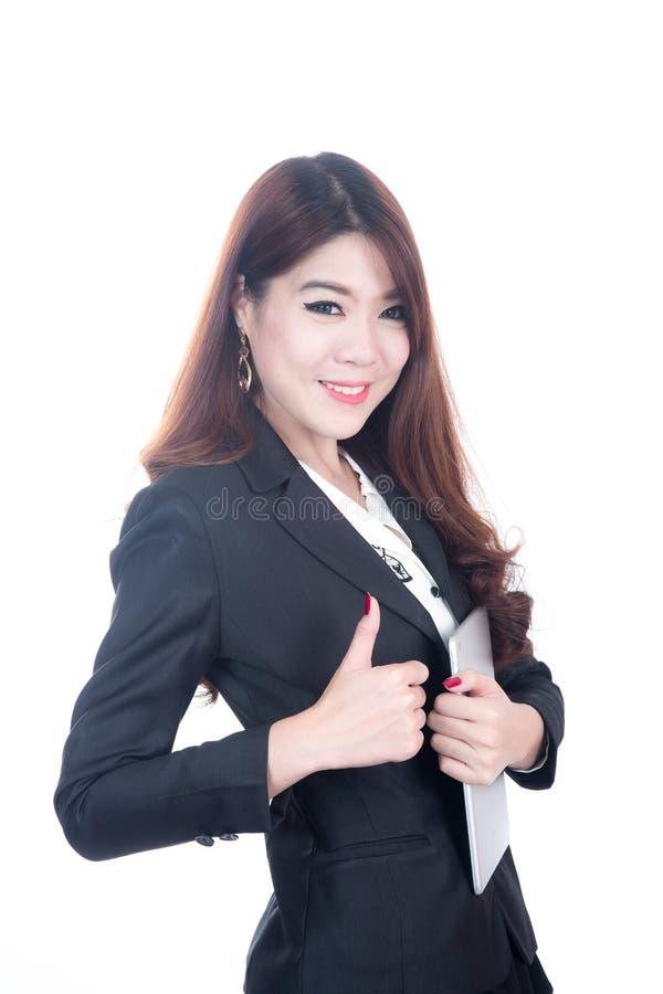 Mulher de negócio que mostra o polegar acima da mão que guarda a tabuleta do computador, conceito do negócio do sucesso foto de stock