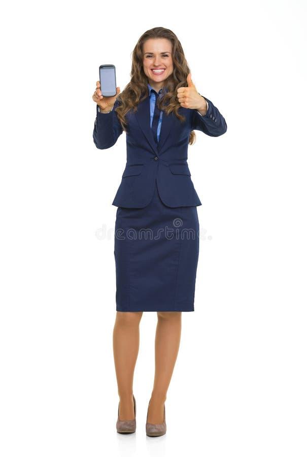 Mulher de negócio que mostra o telefone celular e os polegares acima imagens de stock