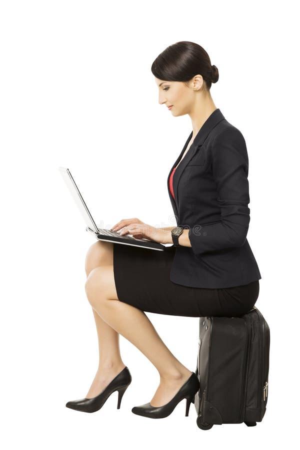 Mulher de negócio que olha o caderno que senta-se na mala de viagem, isolada imagens de stock