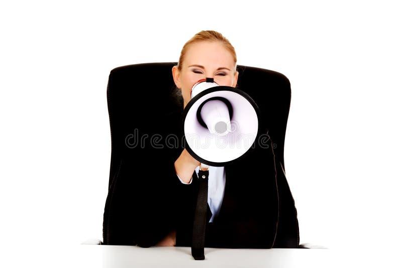 Mulher de negócio que senta-se atrás da mesa e que grita através de um megafone fotos de stock royalty free