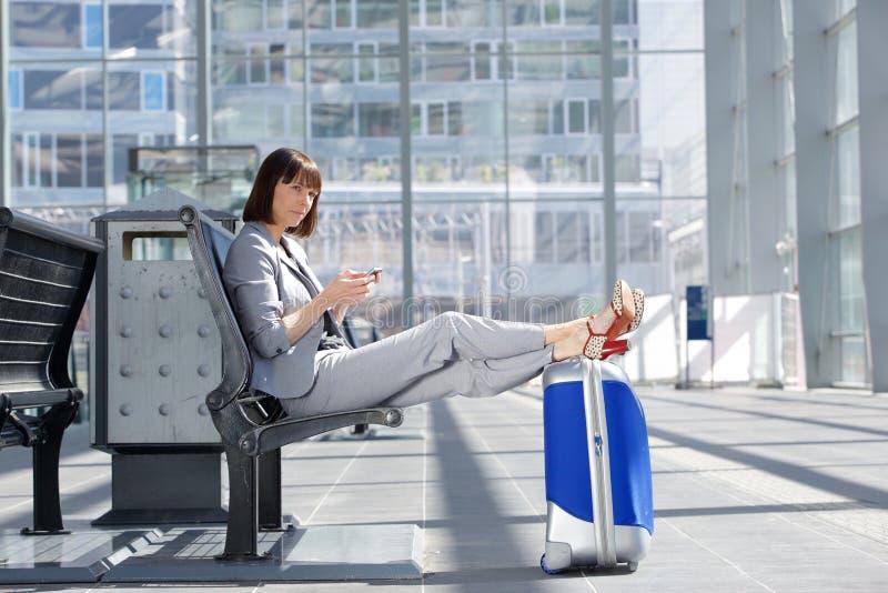 Mulher de negócio que senta-se com telefone celular e saco no aeroporto fotos de stock