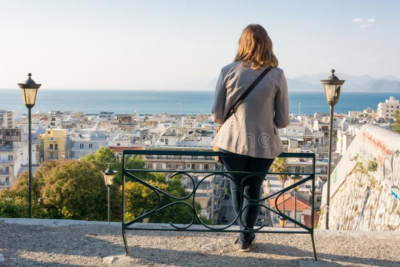Mulher de negócio que senta-se em um banco acima de uma cidade imagens de stock royalty free