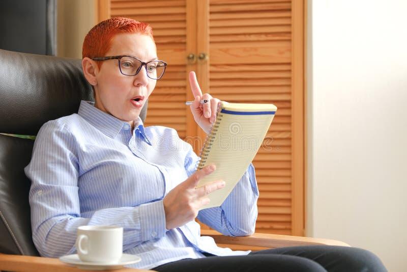 Mulher de negócio que senta-se em uma cadeira Escreve para baixo ideias do negócio, ao lado de uma xícara de café foto de stock royalty free