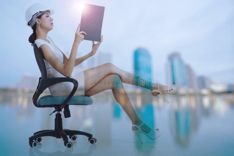 Mulher de negócio que senta-se na cadeira, guardando e olhando a sagacidade do arquivo fotografia de stock royalty free