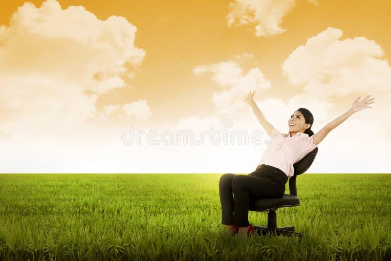 Mulher de negócio que senta-se na cadeira no prado imagem de stock royalty free