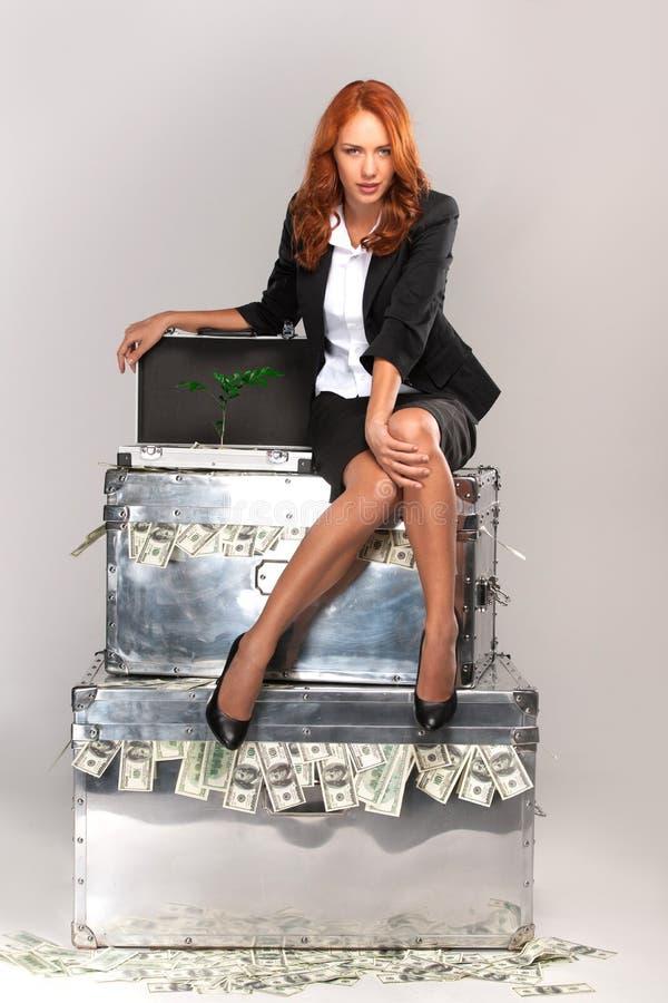 Mulher de negócio que senta-se na mala de viagem completamente do dinheiro fotografia de stock royalty free