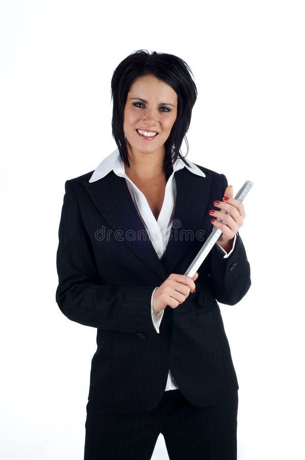 Mulher de negócio que sorri prendendo uma régua do metal fotos de stock royalty free