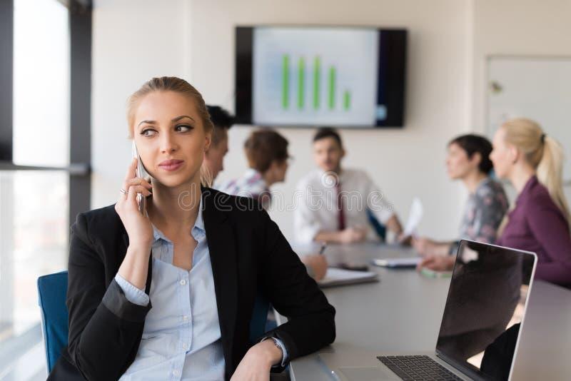 Mulher de negócio que speeking no telefone no escritório com a equipe na reunião fotografia de stock royalty free