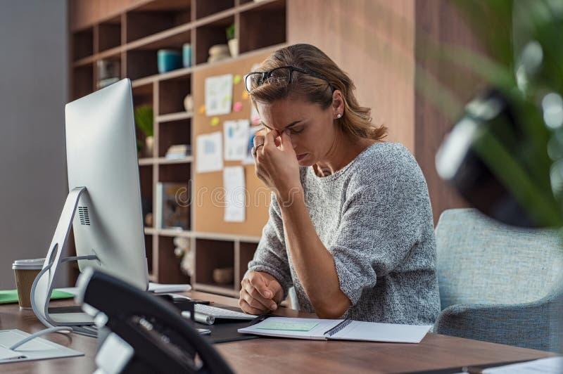 Mulher de negócio que tem a dor de cabeça no escritório fotografia de stock