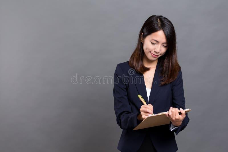 Mulher de negócio que toma a nota na prancheta fotografia de stock royalty free