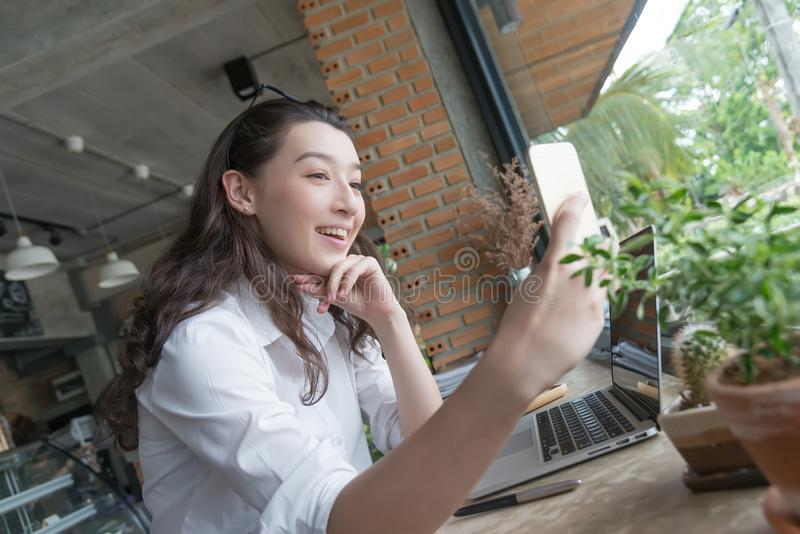Mulher de negócio que toma o selfie no telefone esperto no tempo da ruptura de café em seu lugar de trabalho conceito de mercado  imagens de stock