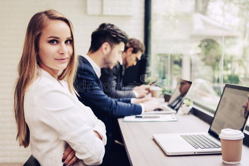 Mulher de negócio que trabalha com a equipe do negócio pelo laptop Seja fotos de stock royalty free