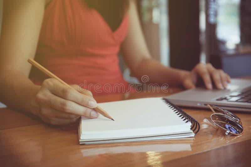 Mulher de negócio que trabalha com original e portátil no escritório imagens de stock