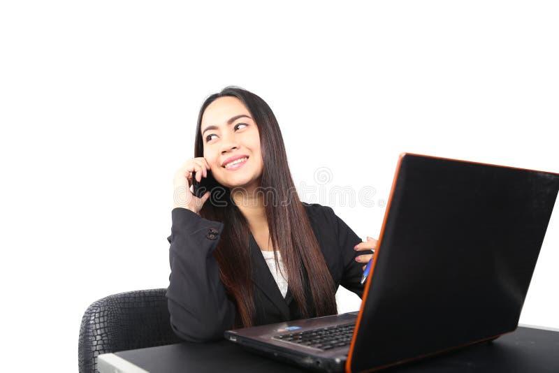 Mulher de negócio que trabalha em seu portátil e que fala no telefone fotos de stock royalty free