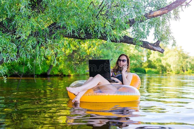 Mulher de negócio que trabalha em um portátil e que fala no smartphone em um anel inflável na água, uma cópia do espaço livre fotos de stock