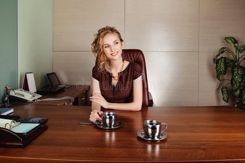 Mulher de negócio que trabalha no escritório e no sorriso fotografia de stock