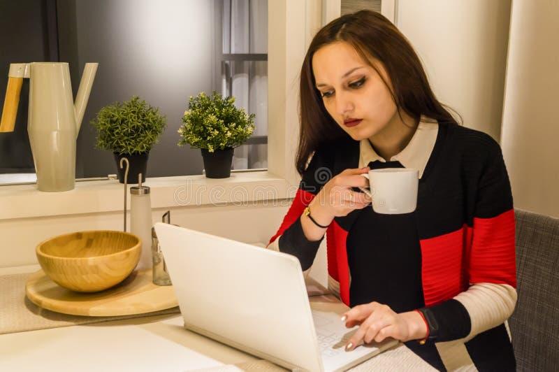 Mulher de negócio que trabalha no portátil e no café quente bebendo foto de stock royalty free