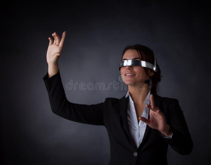 Mulher de negócio que usa óculos de proteção futuristas de VR fotografia de stock royalty free