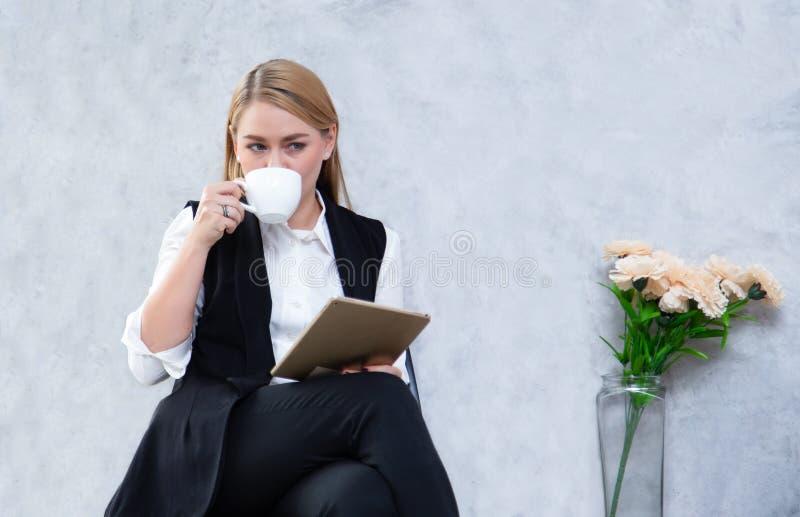 Mulher de negócio que usa o chá digital da tabuleta e da bebida ao sentar-se no café, almofada de toque fêmea atrativa da terra a fotografia de stock royalty free
