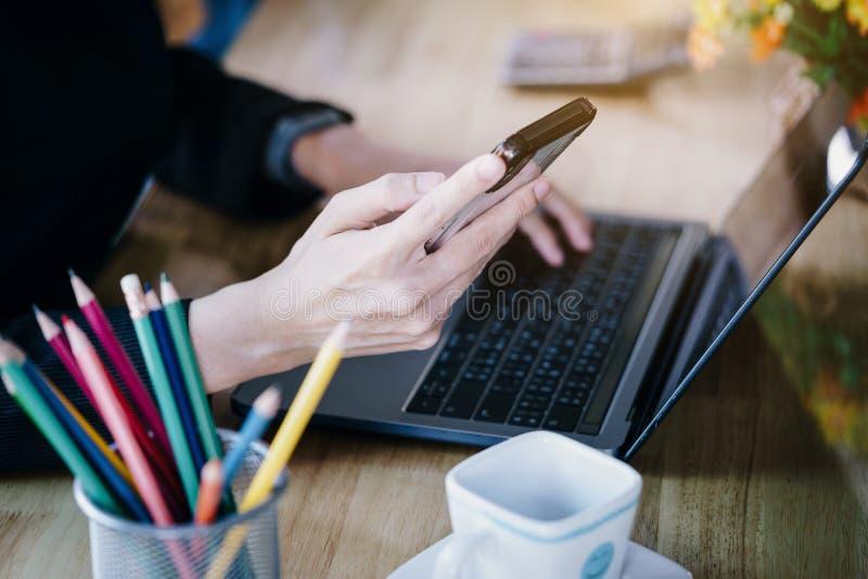 Mulher de negócio que usa o portátil e o telefone celular na tabela no escritório fotografia de stock