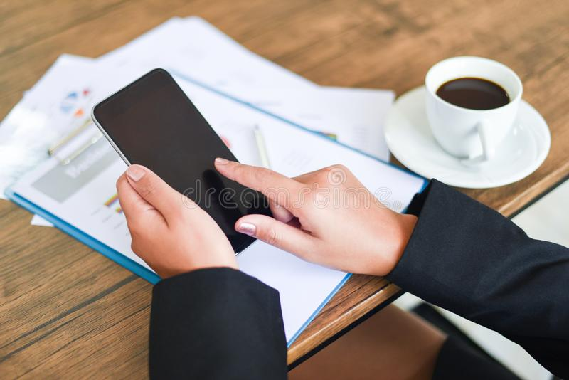Mulher de negócio que usa o smartphone e trabalhando no escritório com relatório comercial na mesa da tabela com copo de café - u fotos de stock