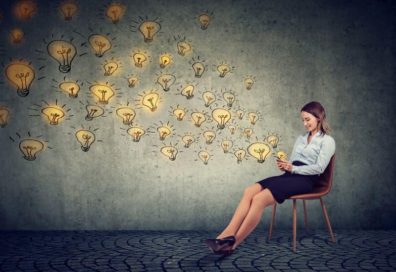 Mulher de negócio que usa o smartphone que envia as ideias brilhantes que são criativas fotografia de stock