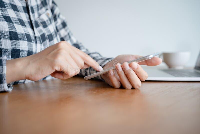 Mulher de negócio que usa o smartphone no escritório da mesa em casa Ao trabalhar moderno da tabela tenha o portátil imagens de stock royalty free
