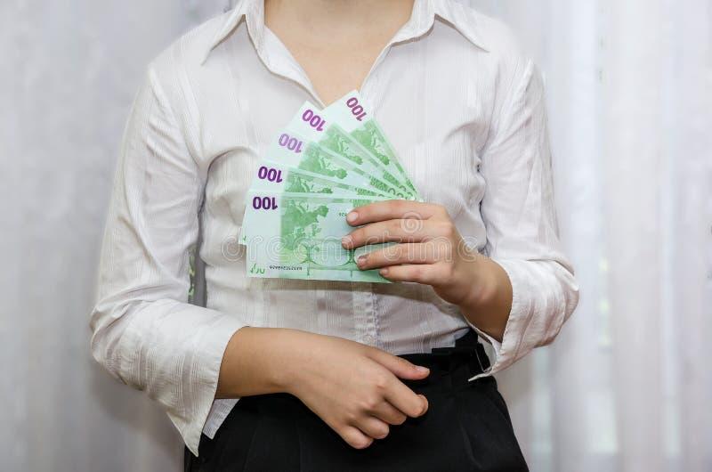 A mulher de negócio realiza em suas denominações da mão de 100 euro imagem de stock