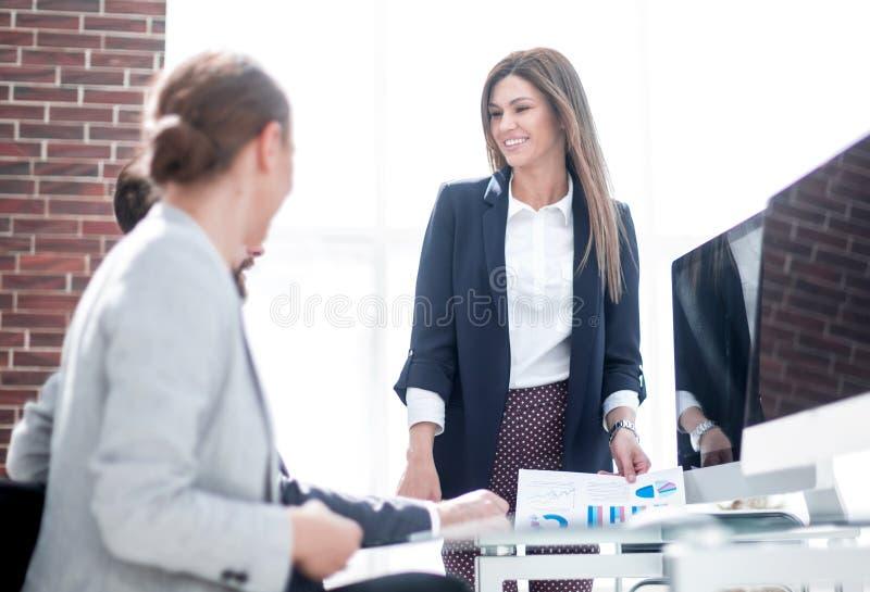 A mulher de negócio realiza uma reunião do funcionamento no escritório fotografia de stock