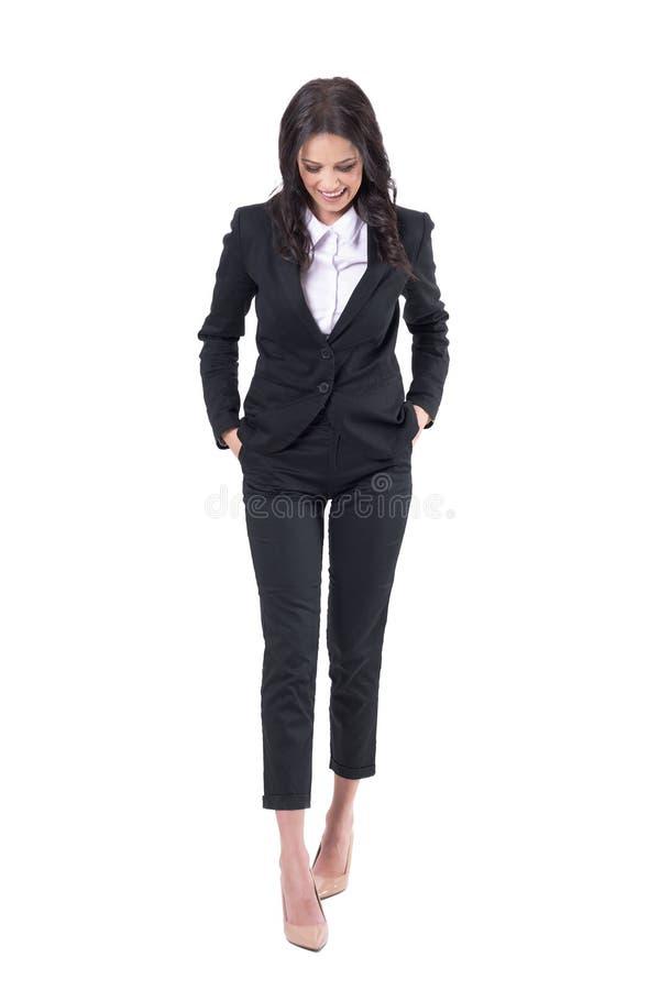 Mulher de negócio relaxado cândido com mãos em uns bolsos do terno que anda e que ri ao olhar para baixo fotos de stock royalty free
