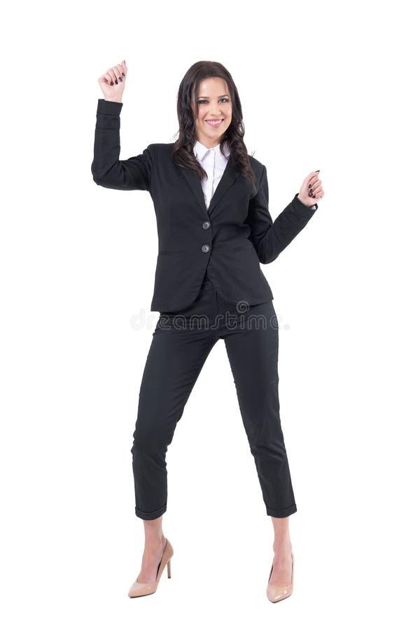 Mulher de negócio relaxado feliz na dança formal do terno que comemora o sucesso com punhos apertados imagem de stock royalty free