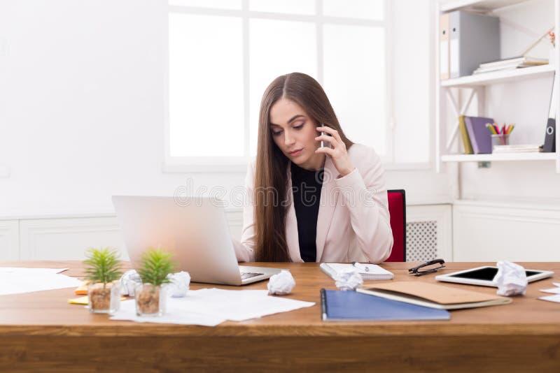 Mulher de negócio séria no trabalho que fala no telefone foto de stock