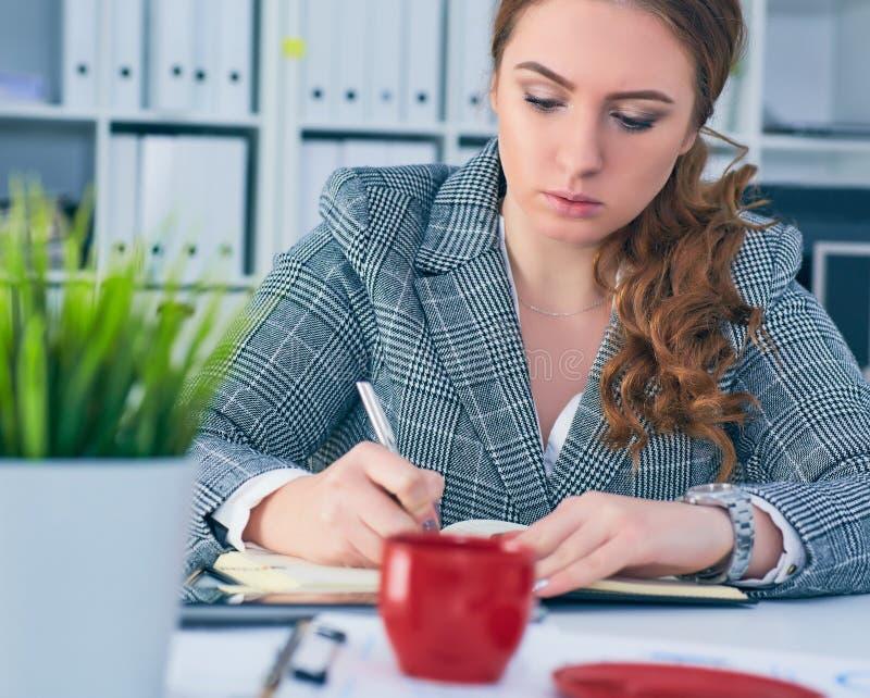 A mulher de negócio séria nova no revestimento escreve na prancheta no local de trabalho no escritório fotos de stock royalty free
