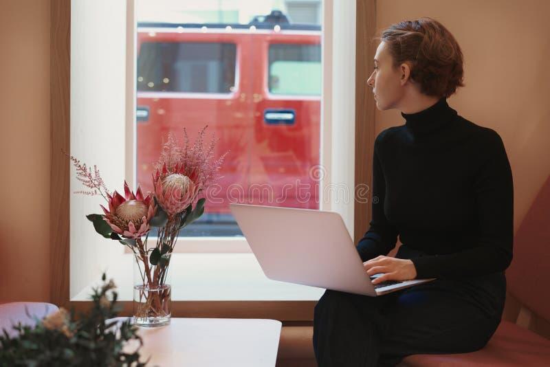 Mulher de negócio séria nova que trabalha no portátil, olhar na janela fora, sentando-se no café, luz do dia fotografia de stock