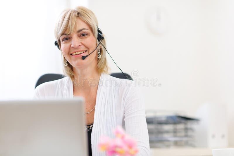 Mulher de negócio sênior com auriculares usando o portátil fotografia de stock
