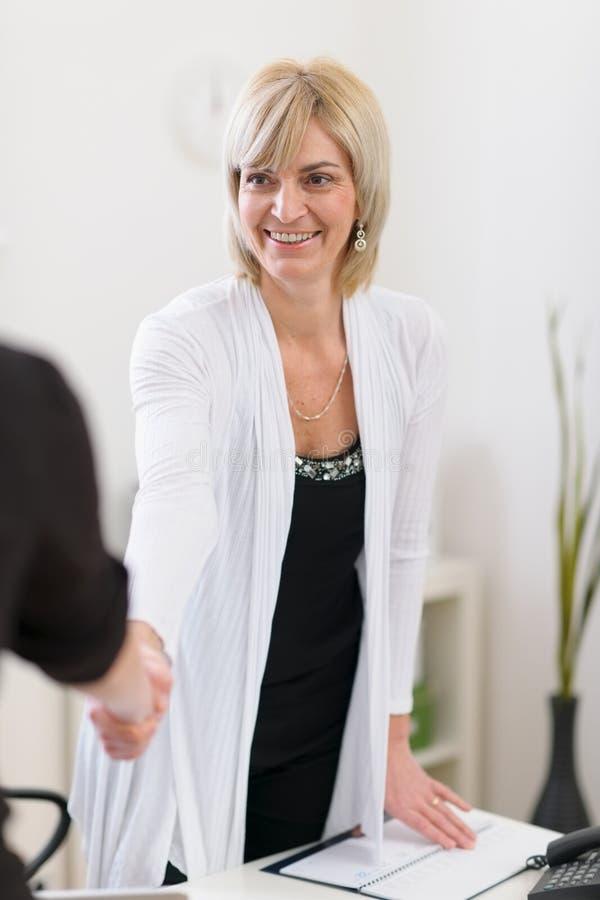 Mulher de negócio sênior que agita a mão dos visitantes imagens de stock