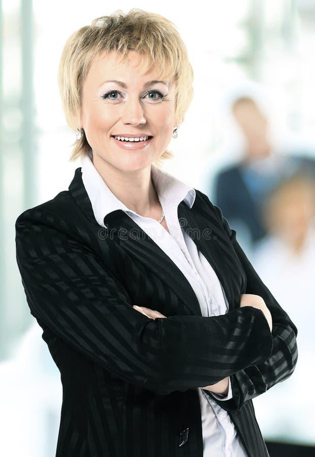 Mulher de negócio segura com na equipe atrás dela fotografia de stock