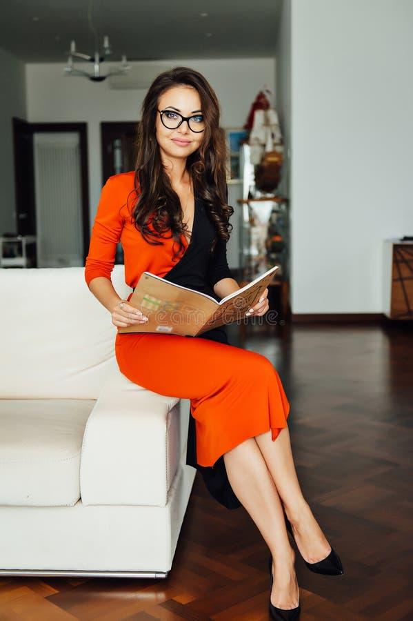 Mulher de negócio 'sexy' mesma que senta-se em um sofá bege em seu escritório imagem de stock royalty free