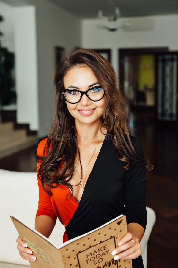 Mulher de negócio 'sexy' mesma que senta-se em um sofá bege em seu escritório imagens de stock