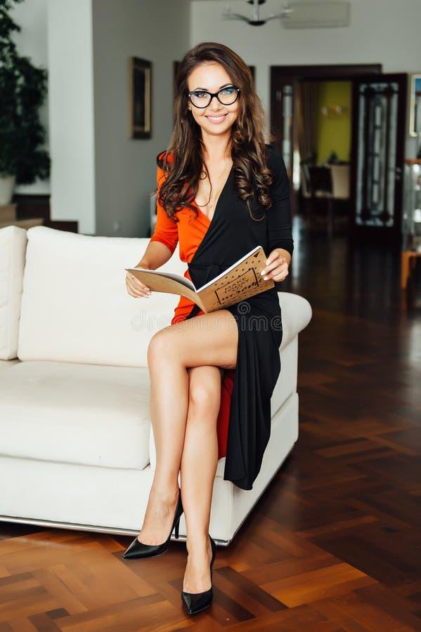 Mulher de negócio 'sexy' mesma que senta-se em um sofá bege em seu escritório fotografia de stock royalty free