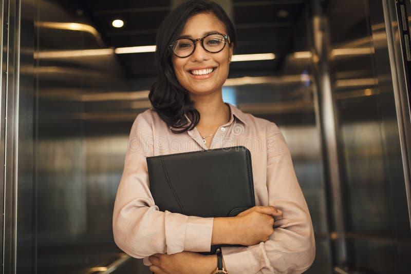 Mulher de negócio de sorriso no elevador do escritório foto de stock royalty free