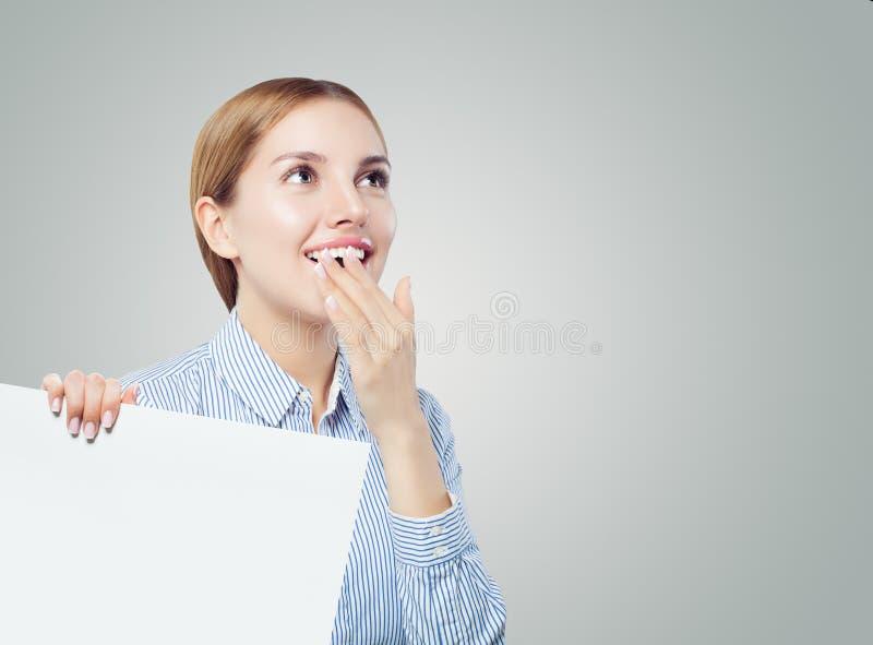 Mulher de negócio surpreendida que olha acima e que mostra o fundo vazio branco da placa com espaço da cópia para anunciar o merc fotografia de stock royalty free