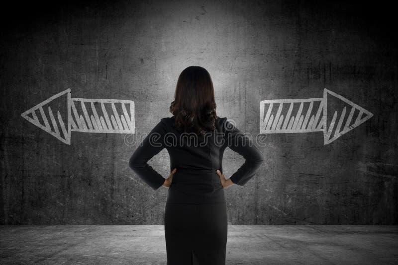 A mulher de negócio tem que escolher entre em dois sentidos imagens de stock royalty free