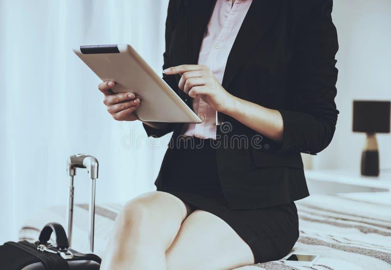 A mulher de negócio usa a tabuleta e o assento na cama foto de stock