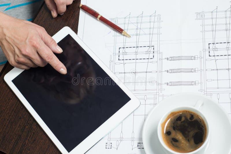 A mulher de negócio usa uma tabuleta e gráficos para o planeamento e a análise de dados do mercado imagem de stock