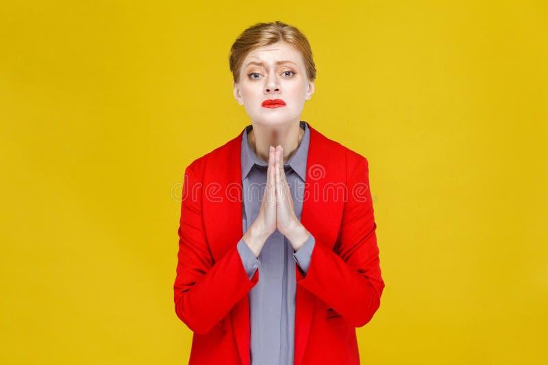 A mulher de negócio vermelha do cabelo no terno vermelho pesaroso, desculpa-se imagens de stock royalty free