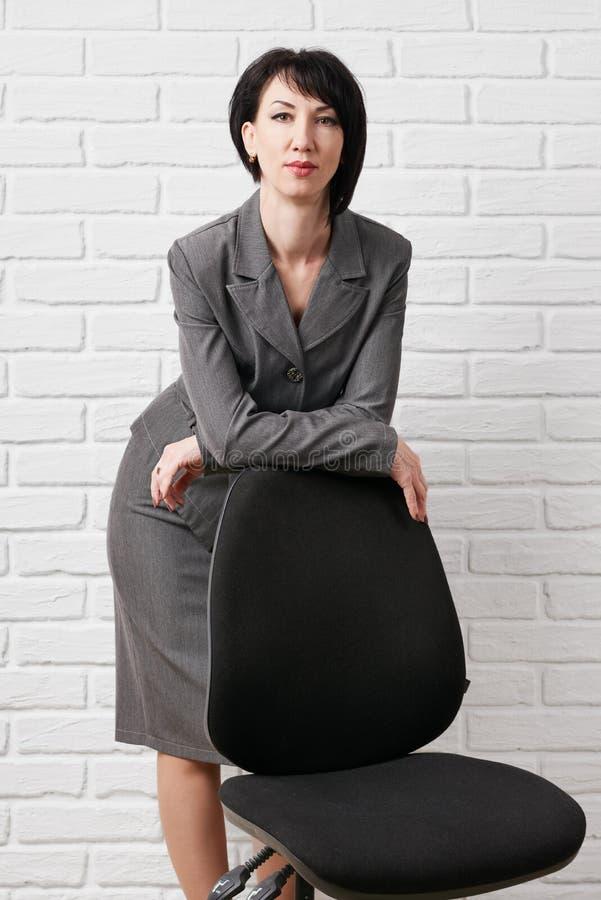 A mulher de negócio vestiu-se em poses de um terno do cinza com uma cadeira na frente de uma parede branca foto de stock