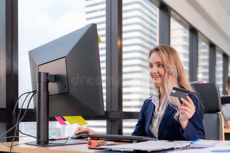 Mulher de negócios à espera de confirmação de sua ordem online no escritório, Blogueiro fazendo compras online e usando cartão de fotos de stock royalty free