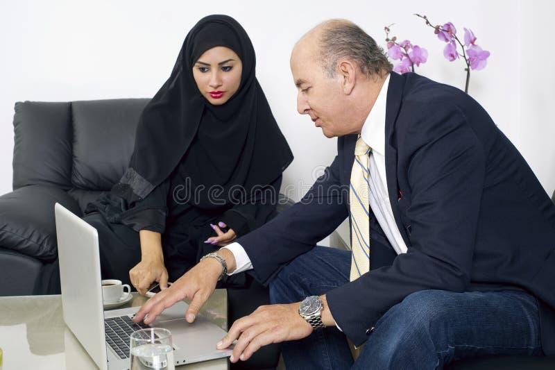 Mulher de negócios árabe no escritório com os empresários que encontram-se no homem de negócios do backgroundSenior que trabalha  imagem de stock