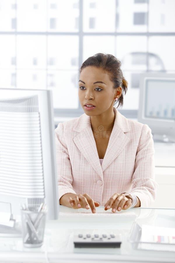 Mulher de negócios étnica que trabalha na mesa foto de stock
